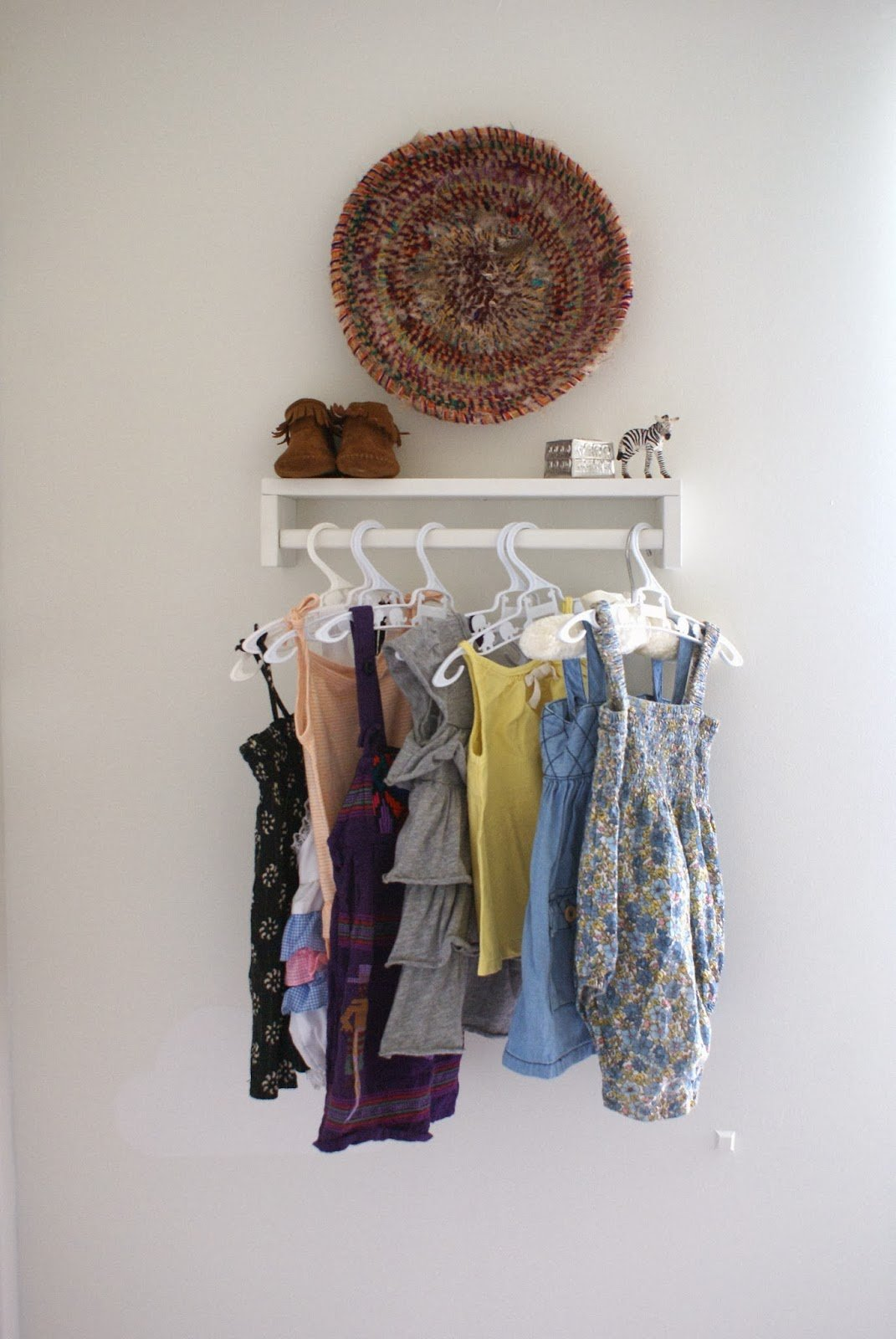2 use a spice rack as a clothing rack for baby clothes via simphome